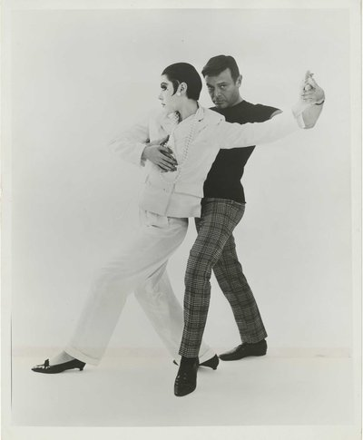 "1|11  Rudi Gernreich with Peggy Moffitt modeling the ""Marlene Dietrich""pantsuit, 1964.Photograph © William Claxton, LLC, courtesy of Demont Photo Management & Fahey/Klein Gallery Los Angeles, with permission of the Rudi Gernreich trademark. Rudi Gernreich papers (Collection 1702). Library Special Collections, Charles E. Young Research Library, UCLA."